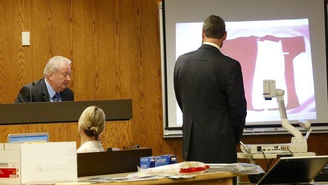 Former Fond du Lac Police detective Milt Swantz testifies Wednesday at the Dennis Brantner murder trial about evidence found in Berit Beck's van. The overhead displays a red shirt, with the back cut out., that has gone missing since the crime occurred in 1990. Fond du Lac County District Attorney Dennis Krueger questions Swantz.