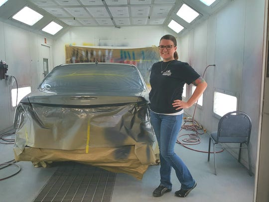 Eden Mays, a graduate and now a teacher in Greenville Tech's auto body repair, poses near a car she helped repair as part of the school's  Recycled Rides program.
