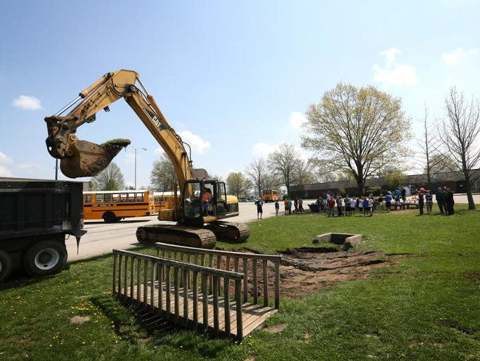 South Oldham Middle School students and teachers watch as excavation is underway to make a rain garden at South Oldham Middle School in Crestwood, Ky. South Oldham Middle School building its own wetland to create an Òoutdoor classroom.Ó Apr. 22, 2014.