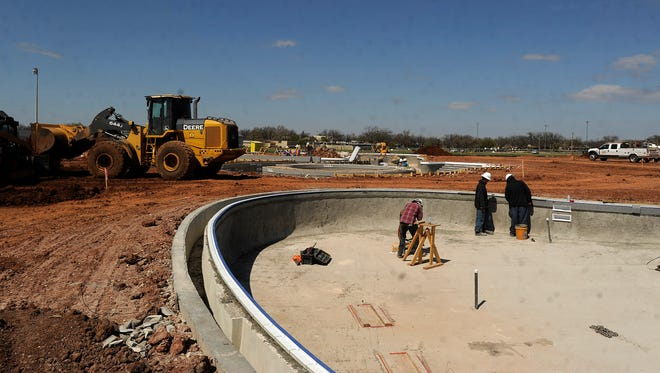 Construction workers work on the City of Abilene's new aquatic center being built at Rose Park on Wednesday, March 15, 2017.