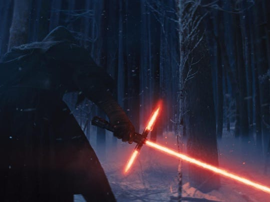 """Adam Driver as Kylo Ren, with his Lightsaber, in a scene from the new film, """"Star Wars: The Force Awakens,"""" in U.S. theaters on Dec. 18. Some theaters are banning masks and face-concealing paint."""