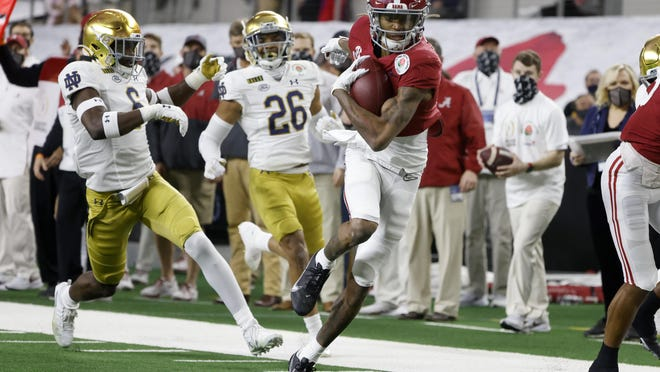 Alabama wide receiver DeVonta Smith (6) gets past Notre Dame linebacker Jeremiah Owusu-Koramoah (6) and cornerback Clarence Lewis (26) on his way to the end zone for a touchdown in the first half of the Rose Bowl NCAA college football game in Arlington, Texas, Friday, Jan. 1, 2021.