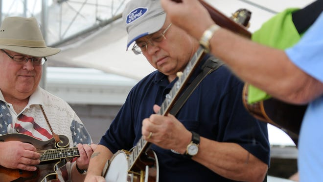 Barry Brincker, of Deckerville, plays with his group, Black River Bluegrass Boys, at the Virginia McNabb Realtor Stage during 2013 Thumbfest in Lexington.