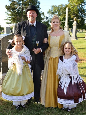 During the 18th annual Candlelight Cemetery Tour, Jerry and Kim Lumpkins portray John and Martha Armfield and their children are portrayed by Rylie Mokros, 9, and Alivia Mokros, 8.