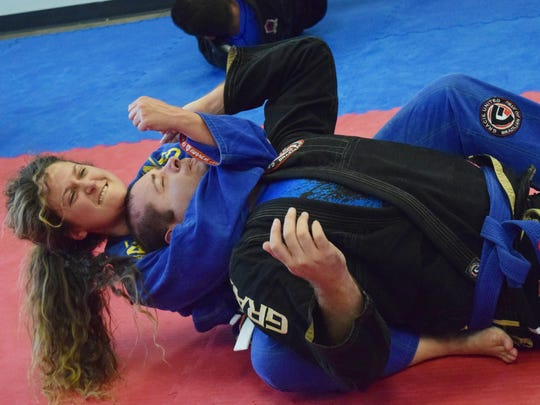 "Rebecca Boyett has Brian Schlmolke in a hold as they  ""roll"" in a Brazilian jiu jitsu class at Gracie United Alexandria Brazilian Jiu Jitsu. ""The more I got into it, I realized that it was a really good self-defense art for men and women,"" said Clint Duplechian, coach at Gracie United. In the classes, women and men are equal when it comes to ""rolling."" ""Nine out of 10 times when a woman is attacked, it will be by a man,"" said Duplechian. ""Rolling"" with men gives women practice in defending themselves against male attackers."