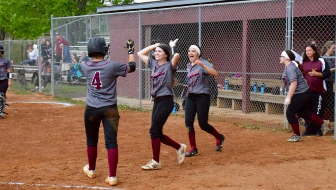 Stuarts Draft's Rendy Dressler, left, is greeted by teammates Courtney Black, center, and Sydney Montoya after scoring the winning run in the Cougars' game against Fort Defiance on Wednesday, April 27, 2016, in Stuarts Draft.