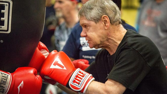Boxer Bob Pardue works on balance and power with the heavy bag. Boxers in the Rock Steady Boxing program rotate between cardio drills in the ring and drills with heavy bags and speed bags.