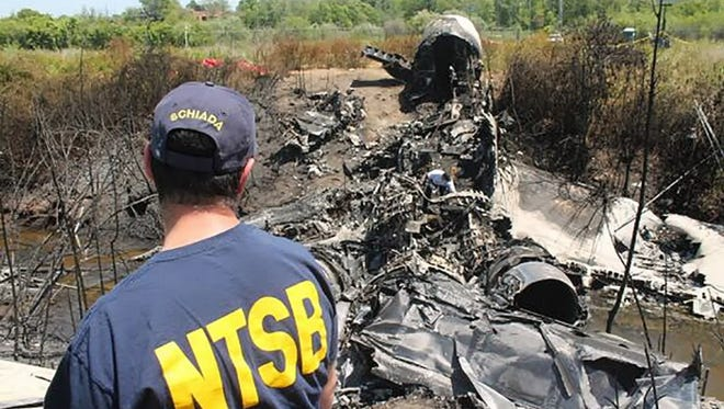 Luke Sciada, a National  Transportation Safety Board investigator, examines wreckage from the fatal crash May 31, 2014, of a Gulfstream IV in Bedford, Mass.