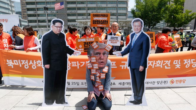 A South Korean wearing a President Trump mask performs during a protest at the U.S. Embassy in Seoul on May 25, 2018.