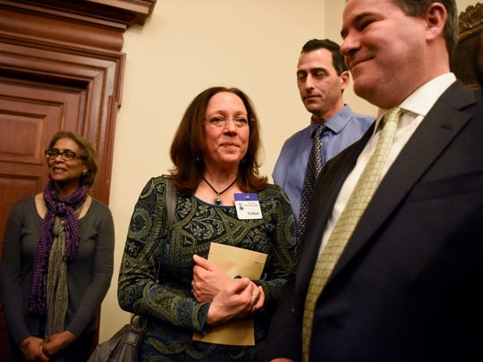 Adoptee Theresa Carroll of East Islip, NY, center, clutches her birth certificate at the end of a press conference held at the State House in Trenton commemorating passage of the NJ Adoptees' Birthright Act. Carroll and Gary Brozowski of Sparta, far right, received their birth certificates at the press conference. The law which allows adopted persons to access their original birth certificate became effective January 1, 2017.