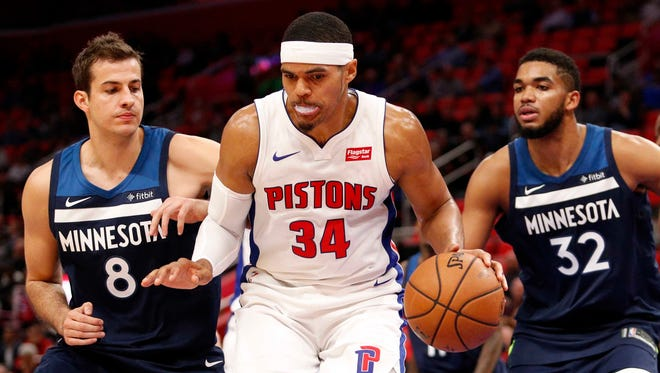 Pistons forward Tobias Harris (34) gets defended by Timberwolves forward Nemanja Bjelica (8) and center Karl-Anthony Towns (32) during the third quarter of the Pistons' 122-101 win over the Timberwolves on Wednesday, Oct. 25,2017, at Little Caesars Arena.