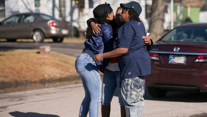 Three well-wishers embrace as they show up outside The Sawmill Saloon, on the 1300 block of North Sherman Drive, the scene of an early morning quintuple shooting Indianapolis, Sunday, Jan. 28, 2018. The women  said they know one of the two people who died at the neighborhood bar.