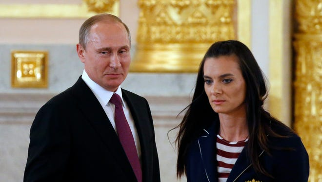 Russian President Vladimir Putin (left) and  pole vaulter Yelena Isinbayeva during a farewell ceremony for the Russian Olympic team at the Grand Kremlin palace in Moscow.