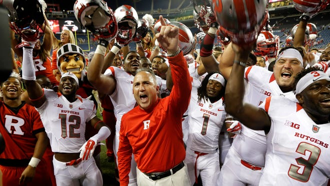 Rutgers head coach Kyle Flood celebrates with his team after the Scarlet Knights beat Washington State.