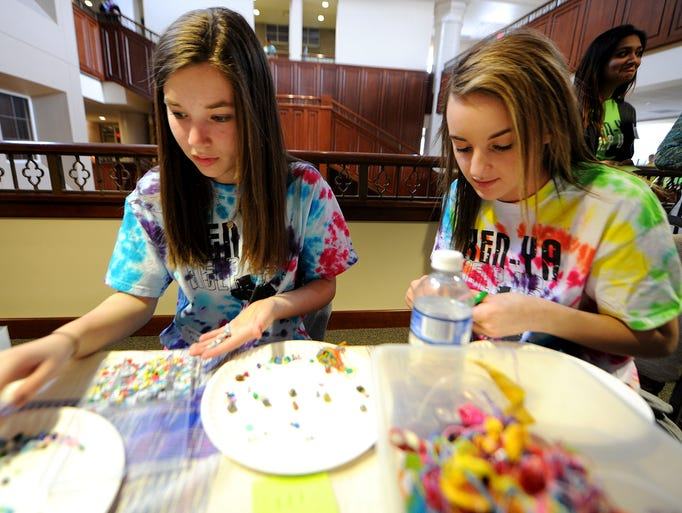 Sydney Glazier, 14, left, and Samantha Snider, 14, make beaded jewelry during the Kenya Carnival, Saturday, March 1, 2014, at Second Presbyterian Church in Indianapolis. The interfaith group of local middle and high school students, their families and congregations raise money and awareness for students who are part of the Umoja Project in Chulaimbo, Kenya.