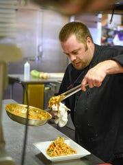 Jason Kurtz plates a dish at the Ace Bar & Grill on