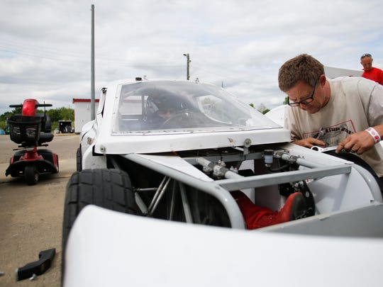 Jeff Parish of Springport adjusts the steering king pins on his son Jon's race car prior to his race Friday, May 26, 2017, at Spartan Speedway in Mason.  Both father and son, as well as Jon's older brother Zach, 15, have hereditary spastic paraplegia.