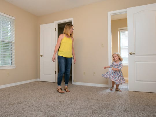 First-time homebuyer Jaime Gibbs watches as her 2-year-old daughter Emma dances in her new bedroom while doing the final walk-through on the house she and her husband are purchasing in Pace on Tuesday, Aug. 8, 2017.
