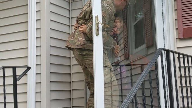 Brianna, 8, smiles as she hugs her father, Michael Eaton, an Easton firefighter, who returned to the family's Franklin home after a four-month deployment in Iraq.