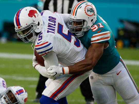 Miami Dolphins defensive end Cameron Wake (91) sacks Buffalo Bills quarterback Tyrod Taylor (5), during the first half of an NFL football game, Sunday, Dec. 31, 2017, in Miami Gardens, Fla.