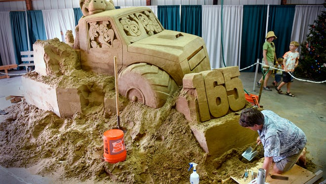 Sculptor Greg Glenn works Wednesday, Aug. 1, on the front of a sand sculpture he is creating at the Benton County Fair in Sauk Rapids. The sculpture, housed in the Discovery Building, reflects the 165th anniversary of the fair and will be finished Saturday.