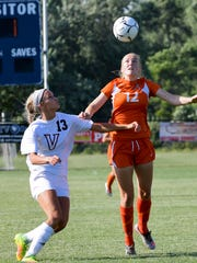 Ames' Catherine Merchant (12) heads the ball as Valley's