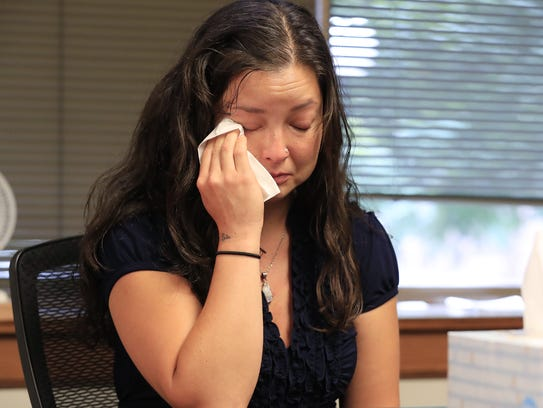 Sarama Teague wipes away tears as she talks about her