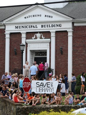 In this 2014 file photo, a rally organized by the Friends of the Watchung Library is held Friday at borough hall to show that Watchung families are willing to spend $1.30 per week for a new library.