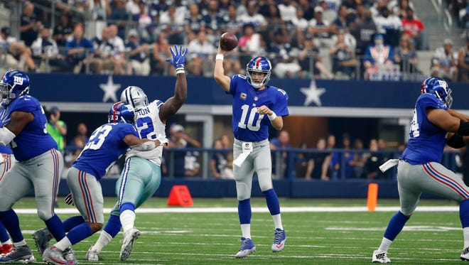 New York Giants quarterback Eli Manning (10) passes as running back Rashad Jennings (23) helps against pressure from defensive tackle Cedric Thornton (92) during an NFL football game, Sunday, Sept. 11, 2016, in Arlington, Texas.