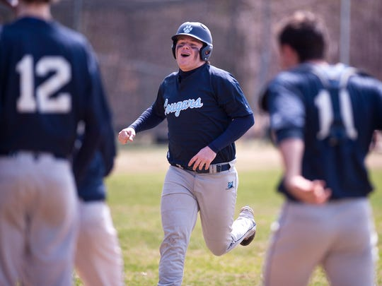 Mount Mansfield sophomore Patrick Burke, center, nears home plate after cracking a solo home run in the fourth inning during Saturday's baseball game in South Burlington.