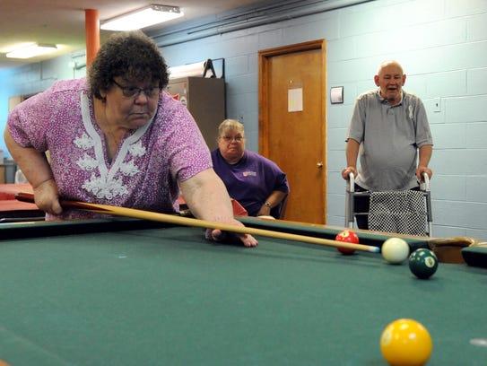 Darlene Cramblit plays pool at the Salvation Army Samartin