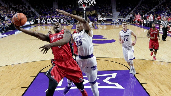 South Dakota's Shy McClelland gets past Kansas State's Wesley Iwundu (25) to put up a shot during the first half of an NCAA college basketball game Friday, Nov. 20, 2015, in Manhattan, Kan. (AP Photo/Charlie Riedel)