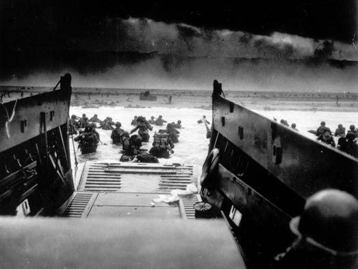 While under attack of heavy machine gun fire from the German coastal defense forces, these American soldiers wade ashore off the ramp of a U.S. Coast Guard landing craft, during the Allied landing operations at Normandy, France on June 6, 1944.