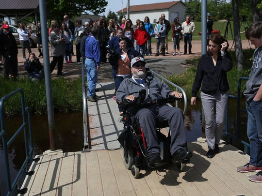 Jim DeBroux motors onto the dock in Mosinee at River Park, Wednesday, May 20, 2015, just before making his first cast with his adaptive fishing pole.