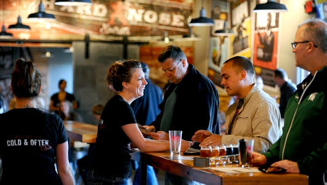 The wait staff greets customers at the grand opening of the Lansing Brewing Company in the Stadium District Thursday 10/22/2015