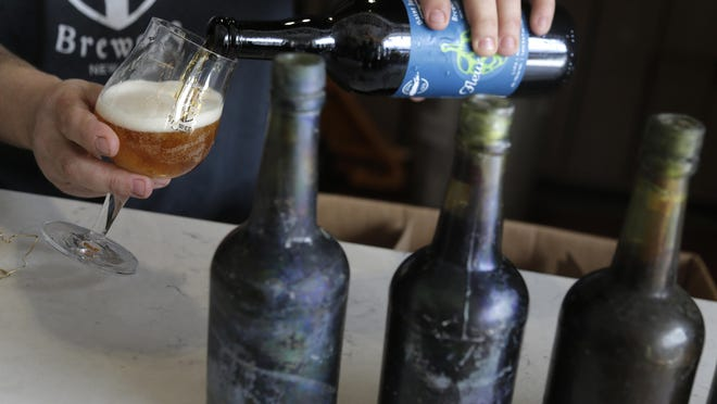 Jamie Adams pours a beer that was brewed using some yeast from beer bottles, right, recovered from the shipwreck of the SS Oregon at his St. James Brewery in Holbrook, N.Y., Monday, March 4, 2019.