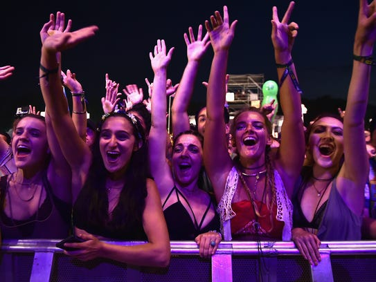 Festival-goers applaud as Mumford & Sons perform during