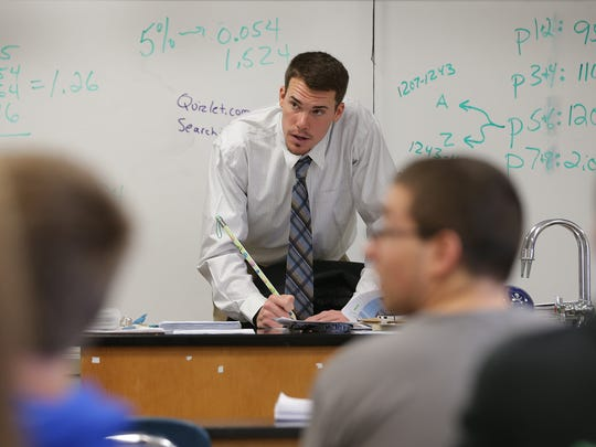 Alex Meyer, substitute teacher and former student at Greensburg High School, takes roll during science class at Greensburg High School.