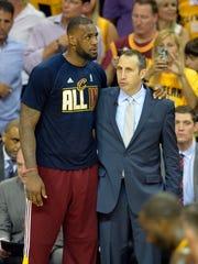 James  talks with Cavaliers coach David Blatt.