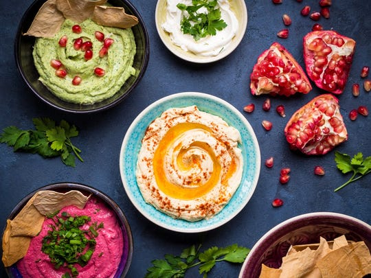Colorful hummus bowls. Different kinds of dips. Traditional hummus, herbs hummus, beetroot hummus, spread. Assorted meze and dips with crispy pita. Meze and snacks concept. Middle eastern snacks set