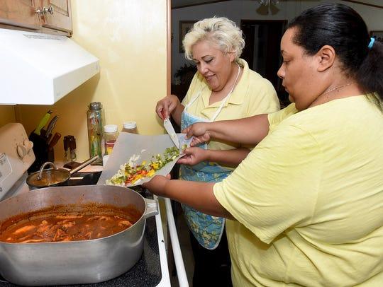 Vanessa Lewis and Hilda Elliott-Brooks prepare a seafood