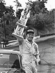 NASCAR driver Jack Ingram with one of the many trophies he won over the years, this one from his home track, New Asheville Speedway, in the 1970s.