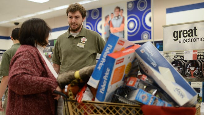 Shopko employee Jacob Meyer answers a question for a Black Friday shopper in the electronics section of Shopko on the East Side of Green Bay in 2014.