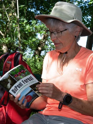 Outdoor writer Danny Bernstein looks through her latest book, DuPont Forest: A History, while sitting on a bench along a hiking trail at Bill Moore Community Park in Fletcher.