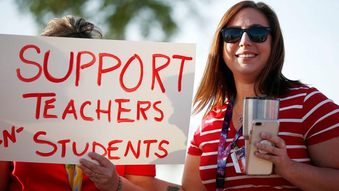 "Stefanie Lowe, a teacher at Tuscano Elementary School in Phoenix, smiles April 11, 2018, as she joins other teachers, parents and students to stage a ""walk-in"" for higher pay and school money. To help make ends meet, Lowe is also a Lyft driver."