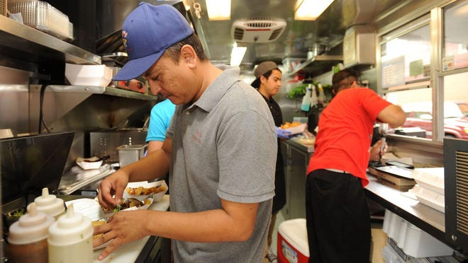 Jesus Rios (left) fills a customer's order while working at Yeyo's Mexican Grill west of the Bentonville square. Northwest Arkansas was recently ranked the third best metropolitan statistical area in the country for minority-owned businesses, based on how many there are and how well they perform.
