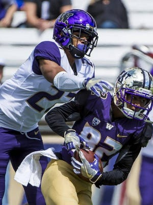 Defensive back Keith Taylor (27) tries to break up a pass caught by wide receiver Jordan Chin (82) during one-on-one drills at the University of Washington football spring preview at Husky Stadium Saturday.