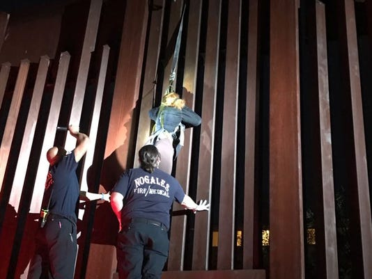Woman dangles from border fence