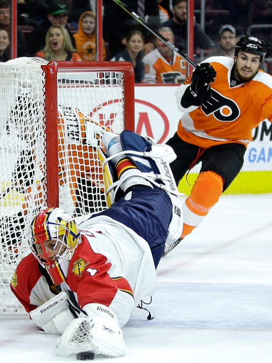 Florida Panthers' Roberto Luongo, left, dives to cover up a loose puck as Philadelphia Flyers' Zac Rinaldo skates in during the second period of an NHL hockey game, Thursday, Nov. 6, 2014, in Philadelphia. (AP Photo/Matt Slocum)