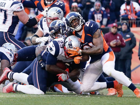 Dec 18, 2016; Denver, CO, USA; New England Patriots running back LeGarrette Blount (29) dives for a touchdown as Denver Broncos cornerback Aqib Talib (21) and inside linebacker Corey Nelson (52) defend in the second quarter at Sports Authority Field at Mile High. Mandatory Credit: Isaiah J. Downing-USA TODAY Sports